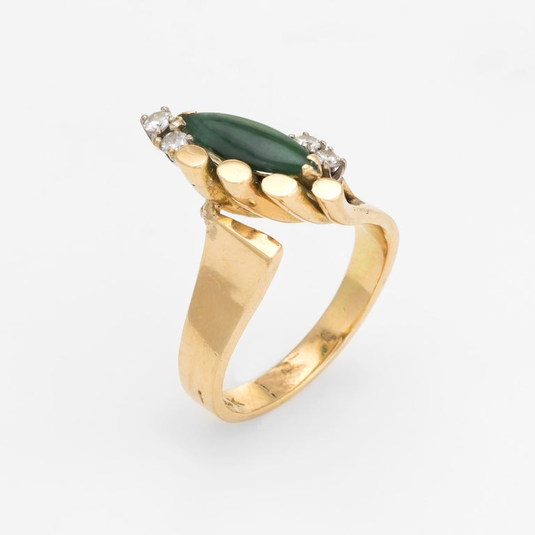Finely detailed vintage jade & diamond cocktail ring (circa 1970s), crafted in 14 karat yellow gold.   Centrally mounted marquise cut cabochon jade measures 13mm x 4mm (estimated at 1 carat), accented with four estimated 0.03 carat round brilliant