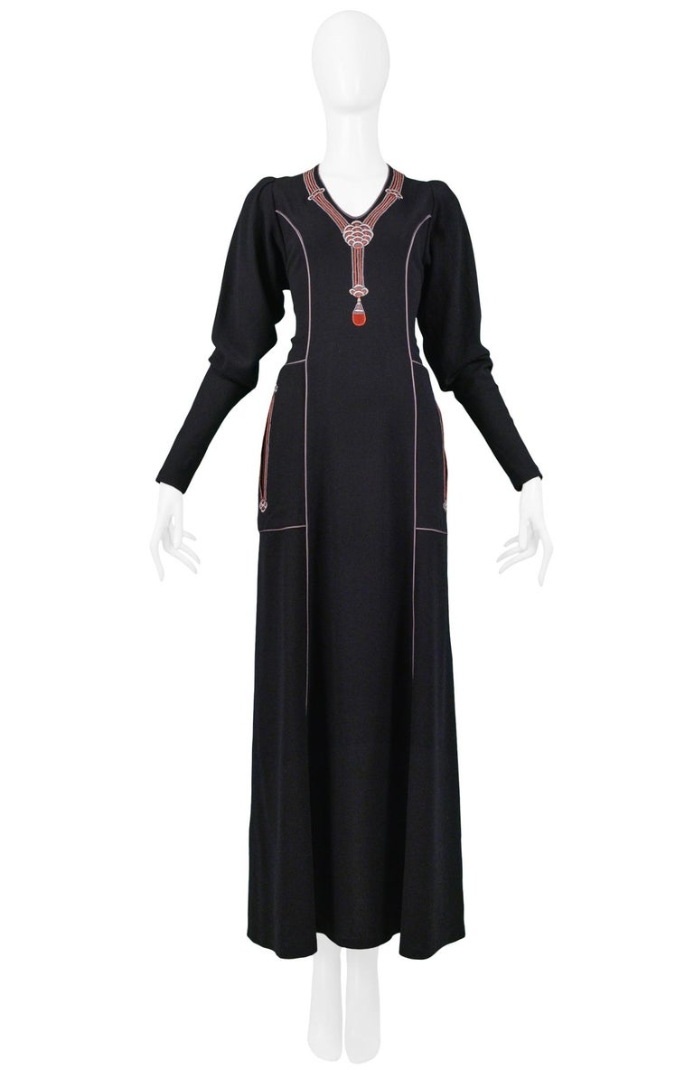 Vintage Janice Wainwright Art Deco-inspired black wool long sleeve maxi dress featuring an embroidered pendant necklace at the neckline, front slit pockets, and cord detailing at the seams. Center back zipper closure. Circa 1970s.  Good Vintage