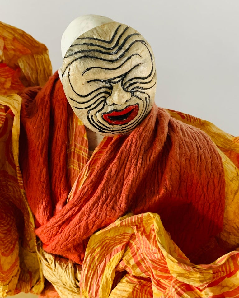 An exceptional vintage Japanese lord or warrior doll or statue handmade of pulled Abaca and rice paper. The lord or warrior has a hand printed face in white and black in that it looks like a zebra design. His traditional outfit died in salmon orange