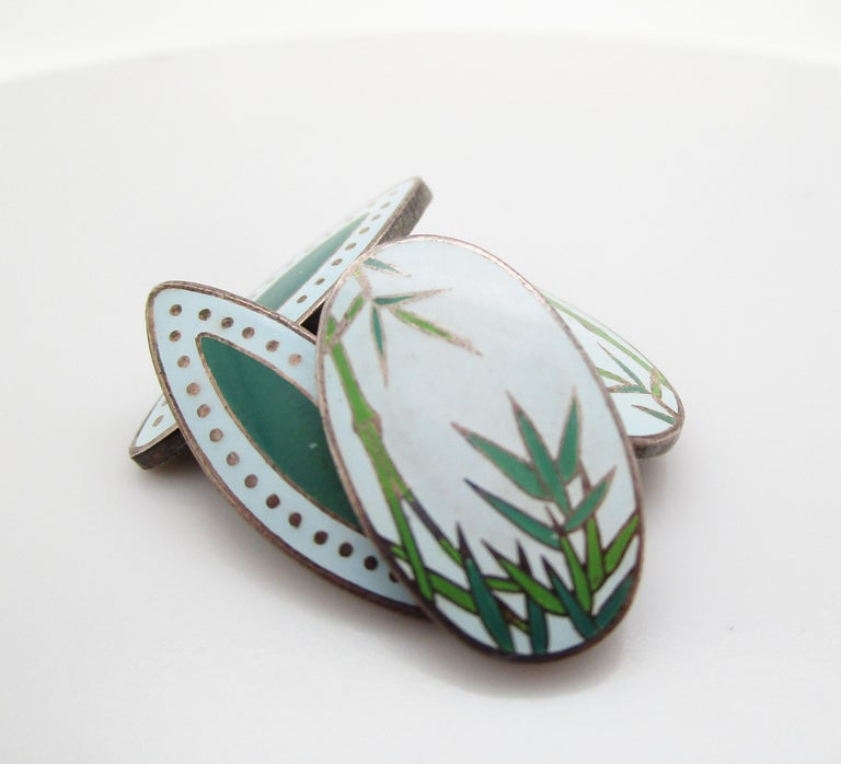 This is an excellent pair of vintage Japanese sterling silver enamel cufflinks with an elegant bamboo pattern. The enamel is in excellent shape and features several shades of green, as well as a soft minty blue shade as the base of the panels. The