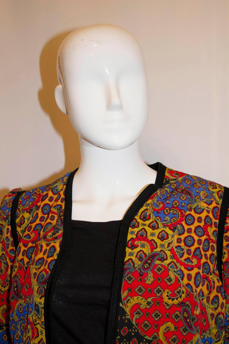 A stunning vintage quilted jacket by Jaeger . In a pretty paisley print with black braid detail, the jacket has a shaped neckline and is fully lined. Measurements:  Bust 37'', length 19''
