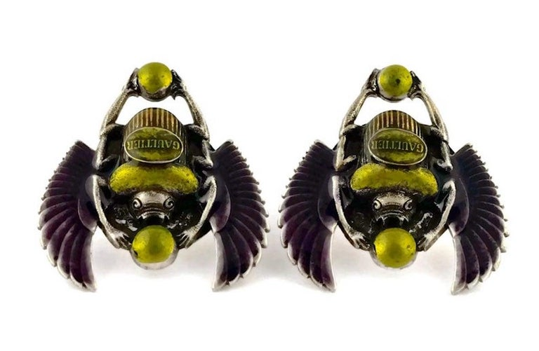 Vintage JEAN PAUL GAULTIER Enameled Scarab Egyptian Earrings  Measurements: Height: 1 5/8 inches Width: 1 4/8 inches  Features: - 100% Authentic JEAN PAUL GAULTIER. - Enameled scarab beetle in olive green and violet. - GAULTIER logo at the centre. -