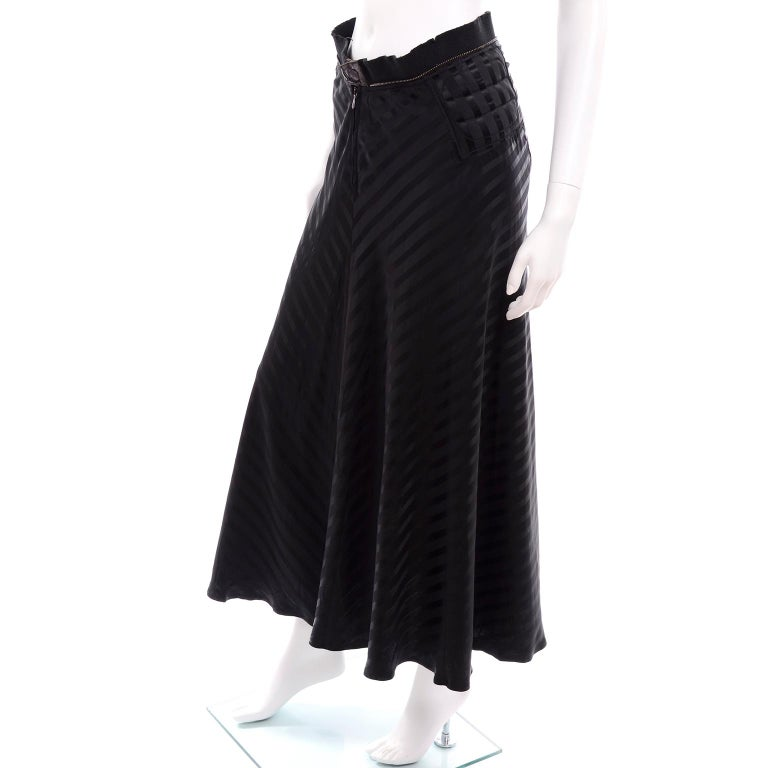This is a versatile vintage Jean Paul Gaultier Femme strapless dress that can also be worn as a skirt.  The dress is in a black 62% Acetate 58% Rayon blend and is labeled a size 4. There is a metal zipper down the front center seam with a metal snap