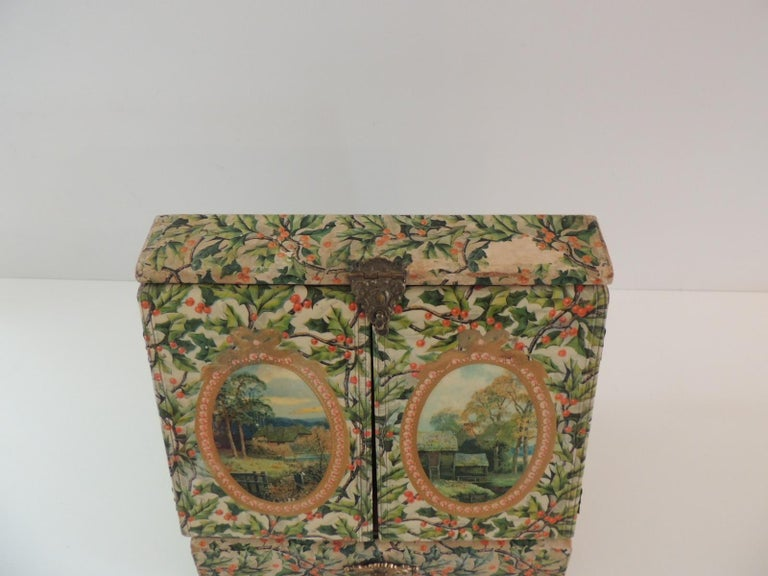 Vintage jewelry box cover in holly pattern paper and laminated doors. Inside mirrors and lining. Red and white rope trim around the mirrors. Drawer in the bottom and delicate brass hardware. Is a beautiful display case. (some parts have missing