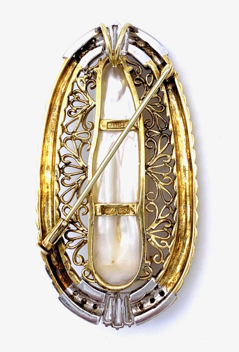 This junky statement pendant can also be worn as a brooch. The wonderful keshi pearl is claw set and surronded by gold wire ornaments within a golden frame designed as a rope. The top and the bottom of the pendant are highlighted by white gold