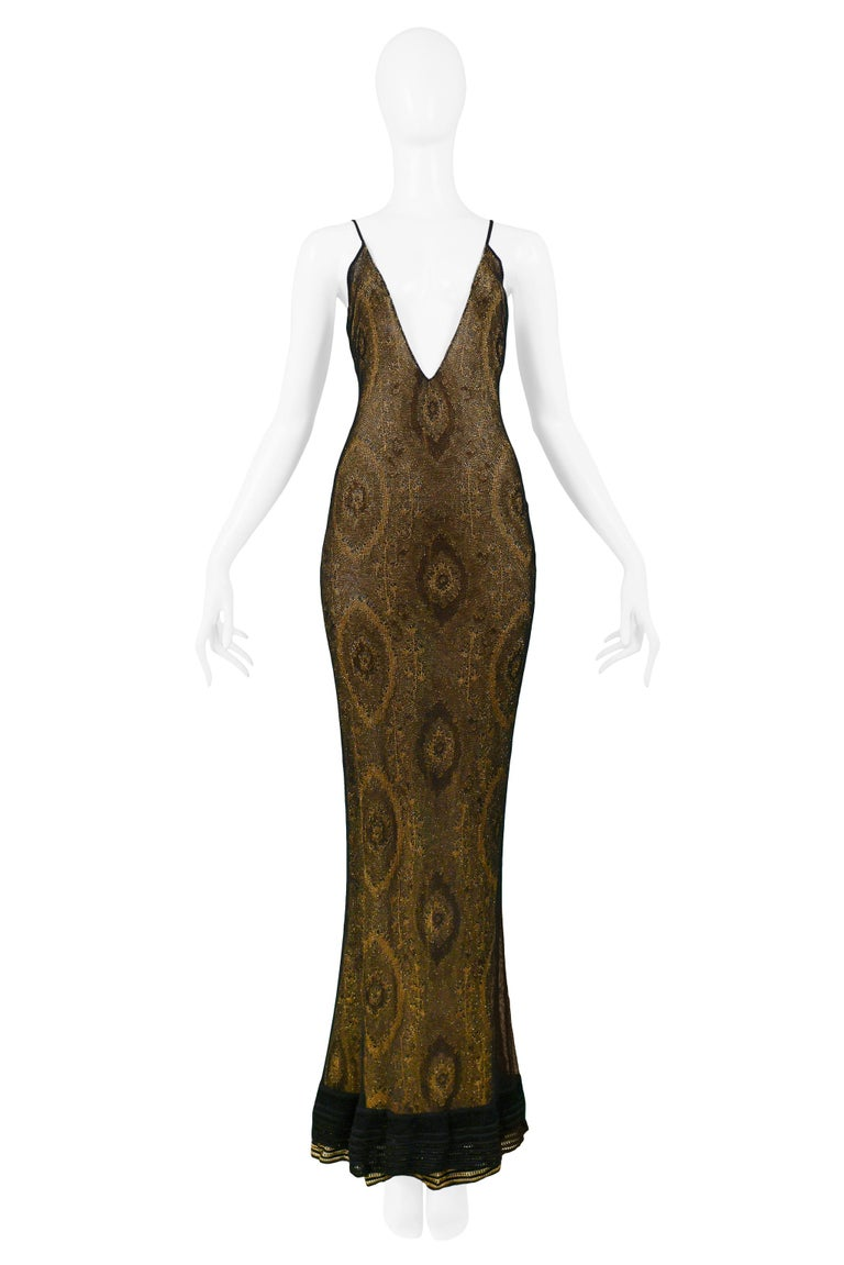 We are excited to offer this vintage John Galliano gold lame netted evening ensemble featuring a form-fitting mermaid evening gown with plunging neckline and back, skinny straps, and black ribber trim at the hem. The dress is offered with a matching