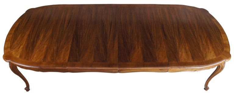 John Widdicomb dining table, circa 1980s. Made from walnut with a serpentine apron over cabriole legs. Features a striking top of exotic Coa matchbook venner from the Hawaiin islands. Draws inspiration from Louis XV and French country / Provincial