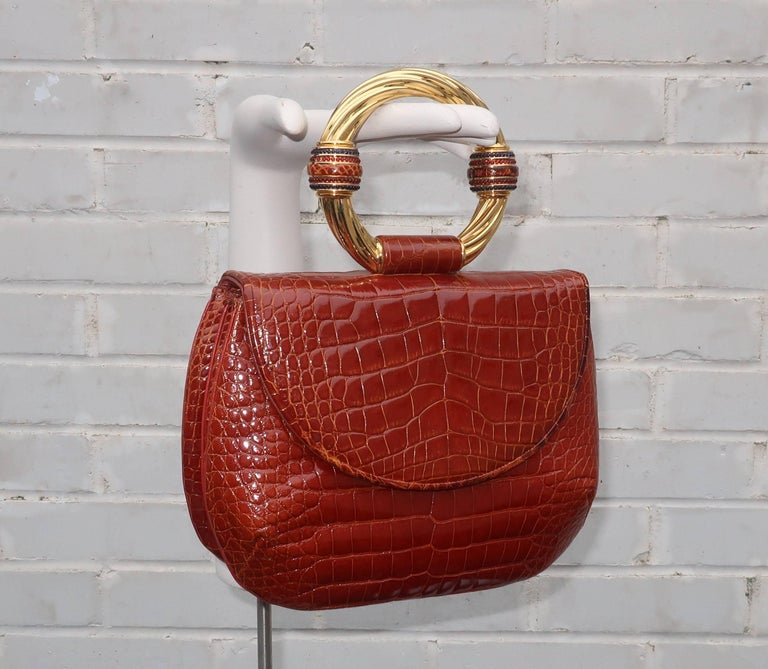 This stunning Judith Leiber alligator handbag serves double duty as a piece of costume jewelry for the wrist.  The versatile cognac colored skin is embellished with a large ring shaped gold tone metal handle.  The handle is decorated with skin and