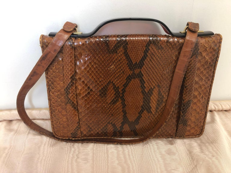 This 1960s/70s snakeskin handbag with a bakelite handle and shoulder strap (removable), is very well kept and has two distinct compartments, one open and the other zipped, as well as a card holder pocket. The interior is pristine and there is only