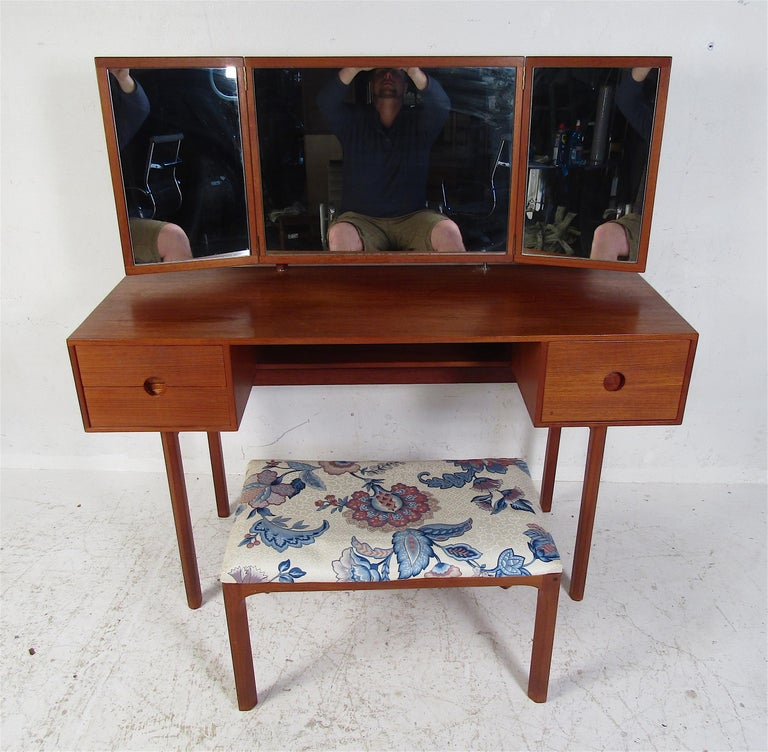 This elegant Mid-Century Modern dressing table includes a matching stool. A unique design with a fold out mirror attached, three hefty drawers with circular recessed pulls, and a finished back. Both the desk and ottoman have been stamped by Aksel