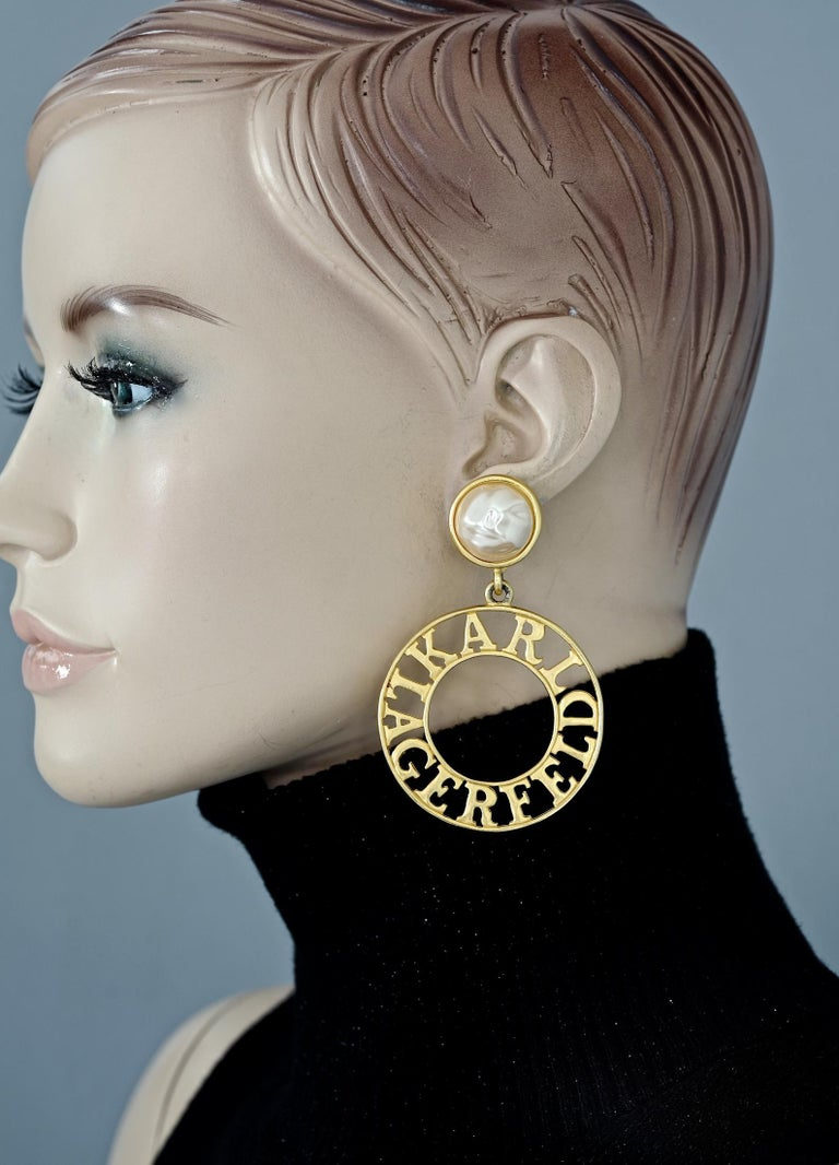 Vintage KARL LAGERFELD Pearl Spelled Out Openwork Hoop Dangling Earrings  Measurements: Height: 3.15 inches (8 cm) Width: 2 inches (5.1 cm) Weight per Earring: 30 grams  Features: - 100% Authentic KARL LAGERFELD. - Glass pearl with KARL LAGERFELD