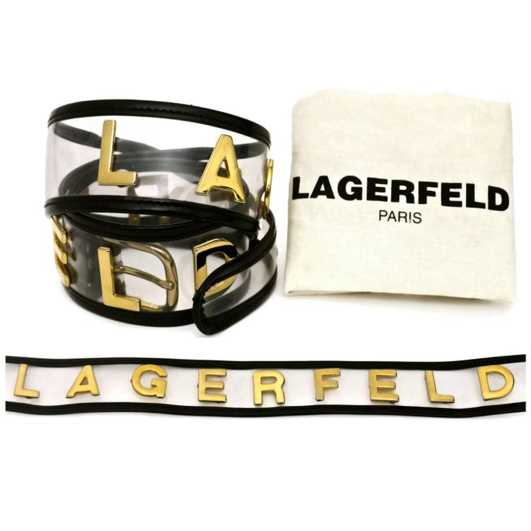 Vintage KARL LAGERFELD Transparent Gold Letter Belt  Measurements: Height: 2 inches Will fit waists: 29 4/8 inches to 32 inches  Features: - 100% Authentic KARL LAGERFELD. - Transparent vinyl and black patent leather trimming. - Spelled LAGERFELD