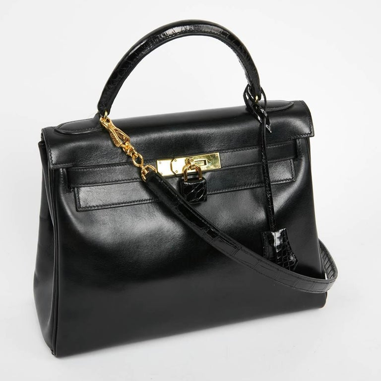 A must-have Kelly 28 bag from Maison Hermès, in a black box leather and alligator. It is worn by hand or shoulder by a removable shoulder strap. The lining is black with 3 pockets, one with zipper. The hardware is golden brass (micro scratches). It