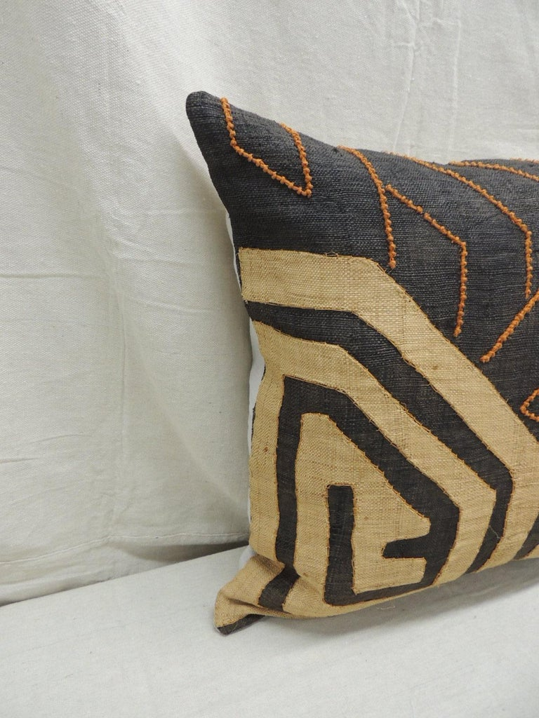 Vintage Kuba orange and black handwoven patchwork African decorative pillow. Handwoven patchwork and appliqué raffia African decorative lumbar pillow with labyrinth pattern and orange beads woven on the textile. Light gris color cotton