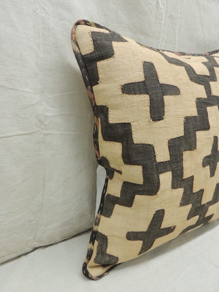 Vintage Kuba tan and black handwoven patchwork African decorative pillow. Handwoven patchwork and appliqué raffia African decorative lumbar pillow with labyrinth pattern. We used the original textile frame as a trim all around the pillow. Light