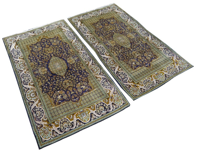 A beautiful pair of vintage Lahore Kashmir bedside rugs in blue green turquoise beige, hand knotted wool and silk.   Construction This pair of bedside rugs has a pile made of fine spun Wool with some small silk highlights. The rugs are very fine