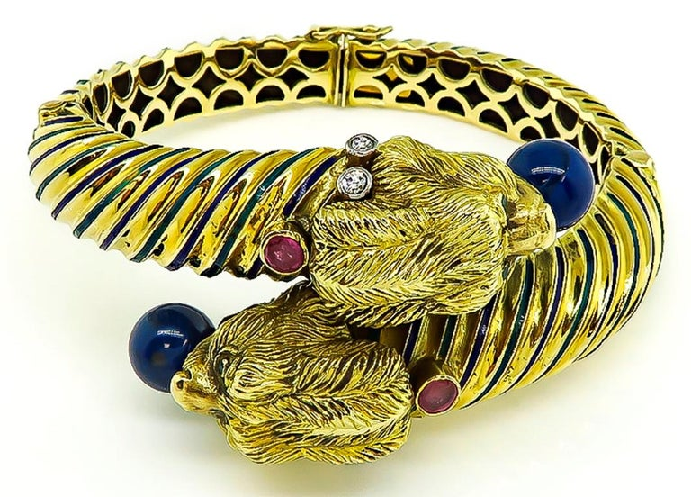 This fabulous 18k yellow gold lion's head bangle from the 1960s. features lovely lapis, ruby and diamond accents. The bangle is stamped 18k and weighs 75.3 grams. The top of the the bangle measures 33mm by 48mm. It will fit a standard wrist