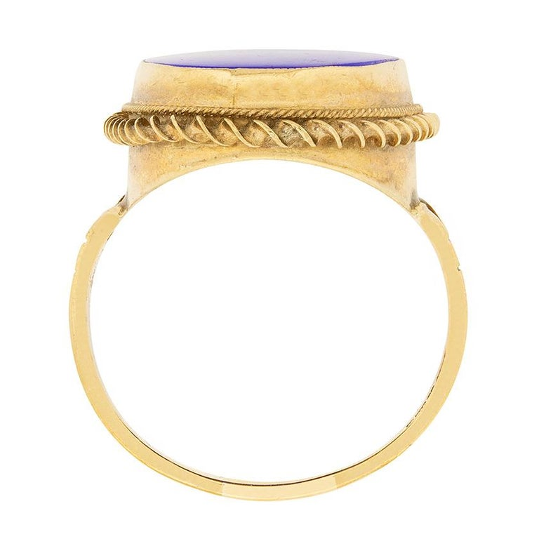 This bold mid-century cocktail ring dates from the 1950s and centres a rich, royal blue, oval-shaped lapis lazuli in a millegrained rubover mounting. The lapis lazuli is surrounded by a handmade frame with a rope and corkscrew design, between