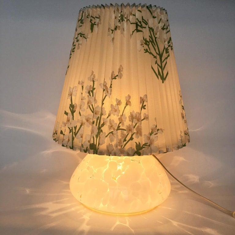 This lamp has two light bulbs one in the shade and one in the glass base. Original cotton/plastic shade.