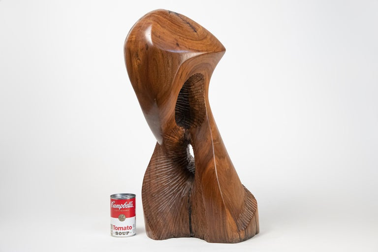 Large carved solid wood abstract sculpture. Unknown artist. Unsigned. Most likely dating to the 1960s. Expertly crafted. Dark colored areas are artist applied wood filler in the wood's natural cracks and gaps. Weighs approximately 25 pounds.