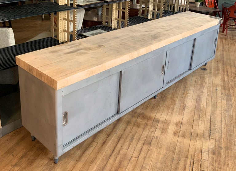 A very nice and well made galvanized steel cabinet with a very thick butcherblock top. The cabinet having full storage behind two pairs of sliding doors, each side with a full width shelf. And the whole raised on steel legs.