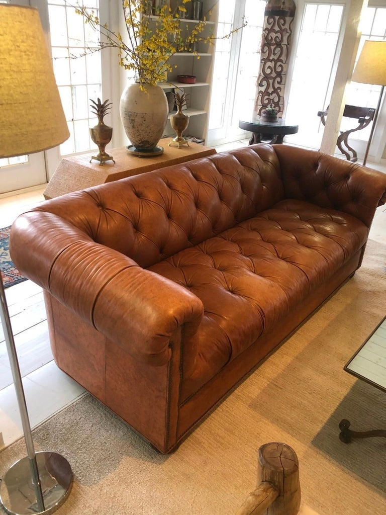 """Classic 1970s Chesterfield sofa in rich caramel color leather. Sofa with large rolled arms and hardwood bun feet Measures: Seat depth 24""""."""