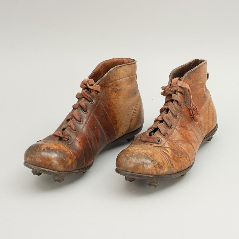 A pair of used tan leather football/rugby boots. The toe area on the boots are made of hardened leather, the sole of the boots are fitted with 6 leather studs. Each stud is formed by layers of leather cylindrical discs fastened to the sole of the