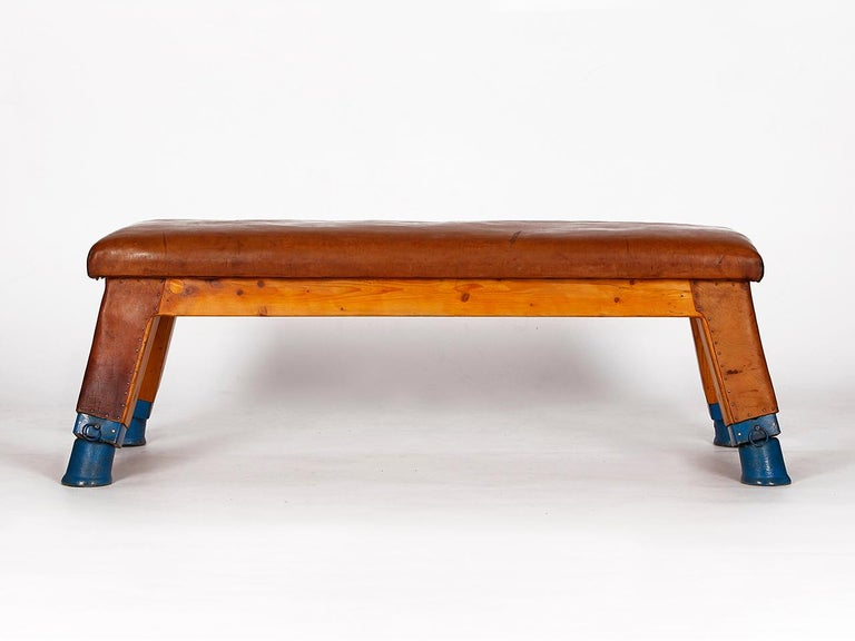 This gymnastics bench comes from a gym in Prague and was designed in the 1930s. The iron feet have been preserved with original cow leather lining. The thick cowhide has been cleaned and preserved and has a very nice patina. Completely restored.