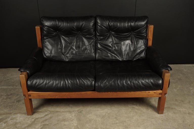 Vintage leather loveseat designed by Pierre Chapo, France 1950s. Solid elm construction with cognac leather straps. Black leather cushions with light patina and wear. Superb quality.