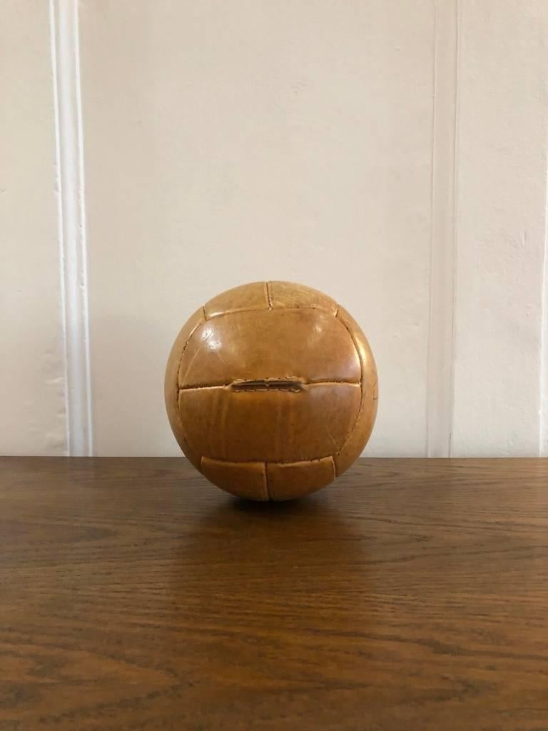 This medicine ball comes from the stock of an old Czech gymnasium. Made in the 1940s. Thick cowhide with patina. Cleaned and treated with a special leather care, writing on surface. Weight: 1kg.