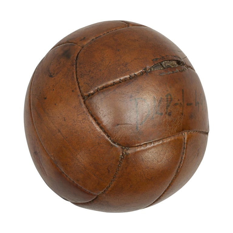 Vintage leather medicine ball. A good vintage leather medicine ball in the shape of a football. It is made from twelve leather panels and the leather has a nice tan polished finish. Written on one of the panels 'DKP - I - S933'. This ball is