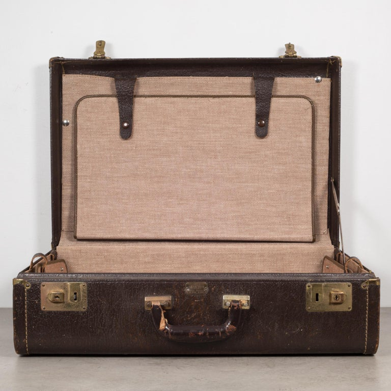 About  An all leather overnight suitcase with stitched corners, leather handle and brass locks. The herringbone interior has three pouches with leather fasteners.   Creator: Travelaire Luggage.  Date of manufacture: circa 1940-1950.  Materials