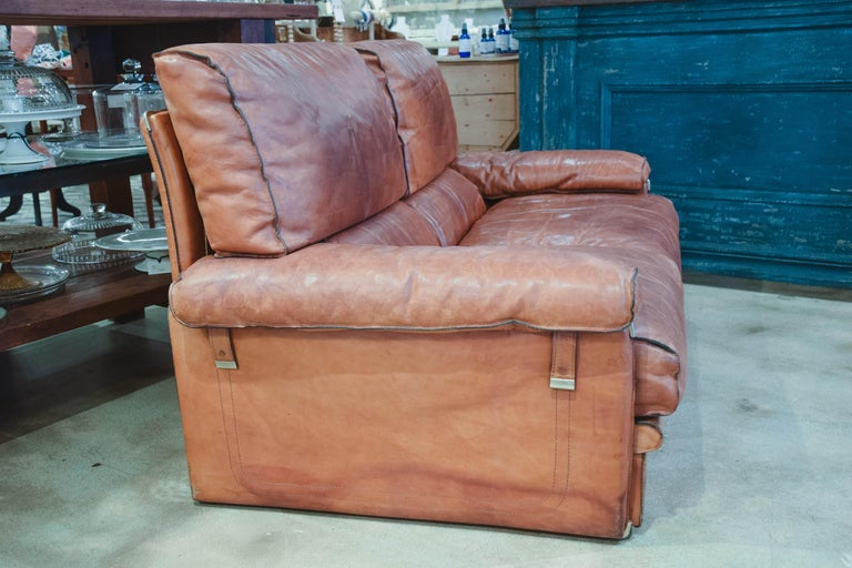 This is a wonderful and comfortable leather sofa in the style of Arcon. The large and comfortable sofa was created in 1970 in leather and offers a beautiful aged patina. The heavy wrapped leather frame shelters soft seats and back cushions, all with