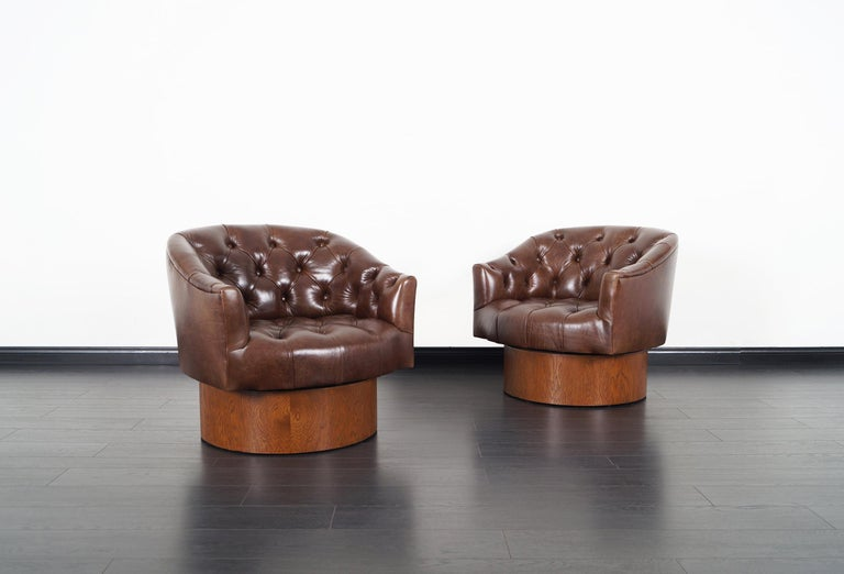 Exceptional pair of vintage swivel lounge chairs designed by Milo Baughman for Thayer Coggin in the United States, circa 1960s. These comfortable chairs have been professionally upholstered in high-quality leather. It features a walnut stain oak