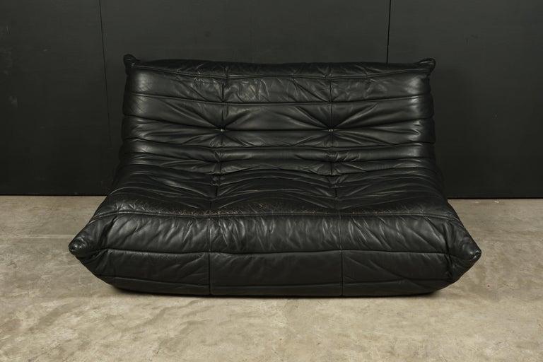 Vintage leather two-seat sofa, model Togo, by Michel Ducaroy for Ligne Roset, France. Original black leather upholstery with original label.