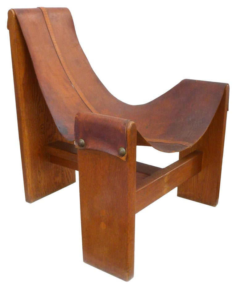 A fantastic, vintage, wood-framed, leather sling chair. A beautiful reduced form; a perfectly-worn, leather sling with exposed centre-seam fastened with oversized brass tacks, draped over a wonderfully-proportioned, elegant wood-board frame. Great