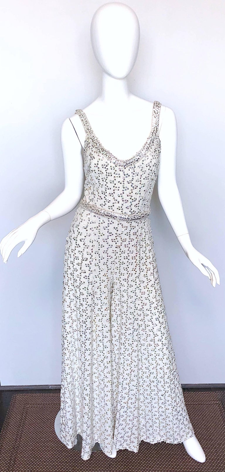 Sensational early 1970s LILLI DIAMOND silver sequined lurex wide leg disco jumpsuit! Features thousands of hand-sewn silver sequins throughout. Soft silver metallic lurex fabric. Fully lined. Fitted bodice, with original detachable belt and wide