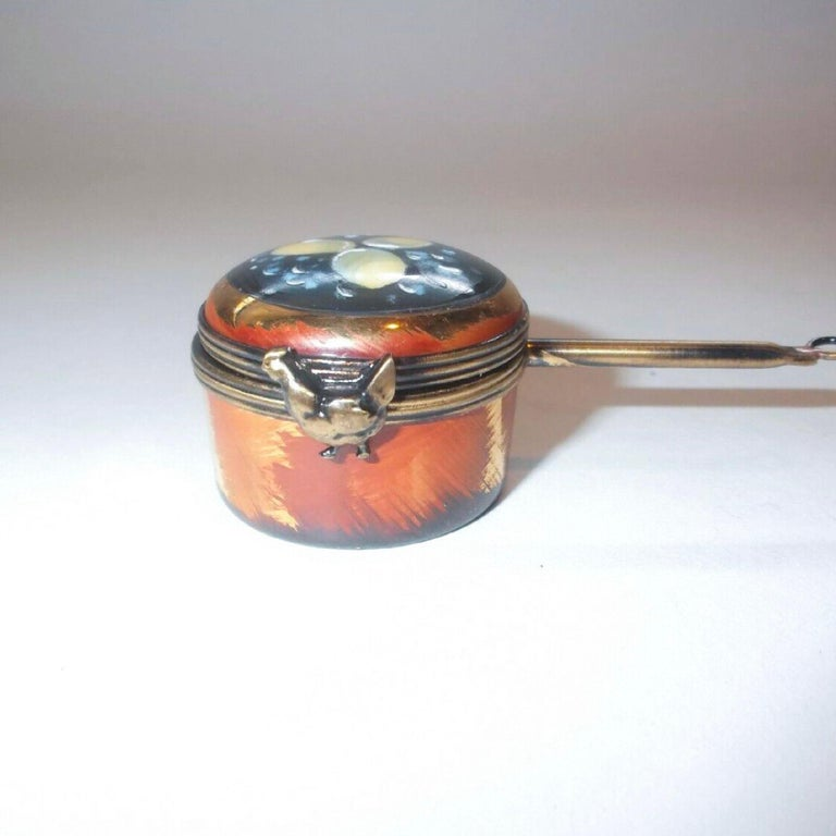 Midcentury handmade Limoges miniature - Copper color saucepan by Lagloriette, long handle with a hanging hook at the end the top of the box is painted with three eggs surrounded by boiling water. The clasp is in the form of a hen. Inside are two