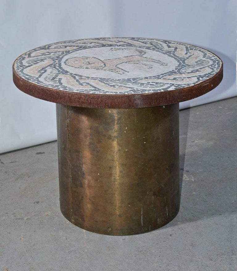The vintage coffee, side or end table is composed of a brass drum base and a round mosaic tile top. The standing lion is encircled by a classical rope pattern. The tile colors are charcoal grey, grey green, tan, soft pink and white. The mosaic