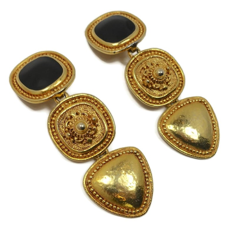 """These vintage earrings feature a black enamel top panel with two carved gold tone drops.  In excellent condition, these clip earrings measure 3-1/4"""" x 1""""."""