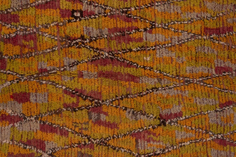 This tribal piece shows a multicolored field with an overlying tall lozenge trellis in brown, greens, and ivory, with soft coral red spots within and set around. This long pile example is in good condition with the flat-woven end panels intact.
