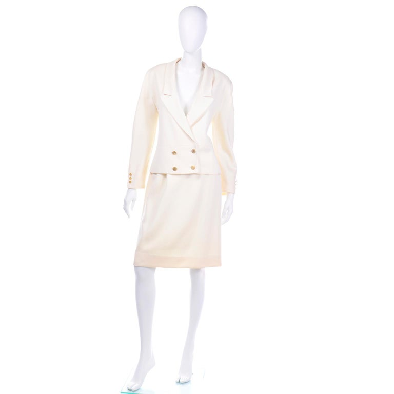 This elegant Louis Féraud cream wool skirt suit is so beautifully made and it comes with a pencil skirt and a double breasted blazer. The jacket has gold tone textured buttons on the cuffs of the sleeves, the double breasted closure and the back of