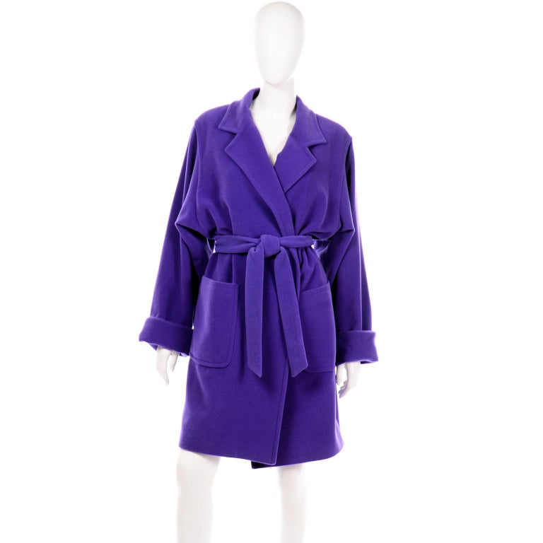 This gorgeous angora wool blend coat is in a beautiful rich jewel tone shade of purple. This trench style coat has a matching fabric belt and deep front pockets. The sleeves are long and wide with big folded cuffs and the coat is fully lined. There