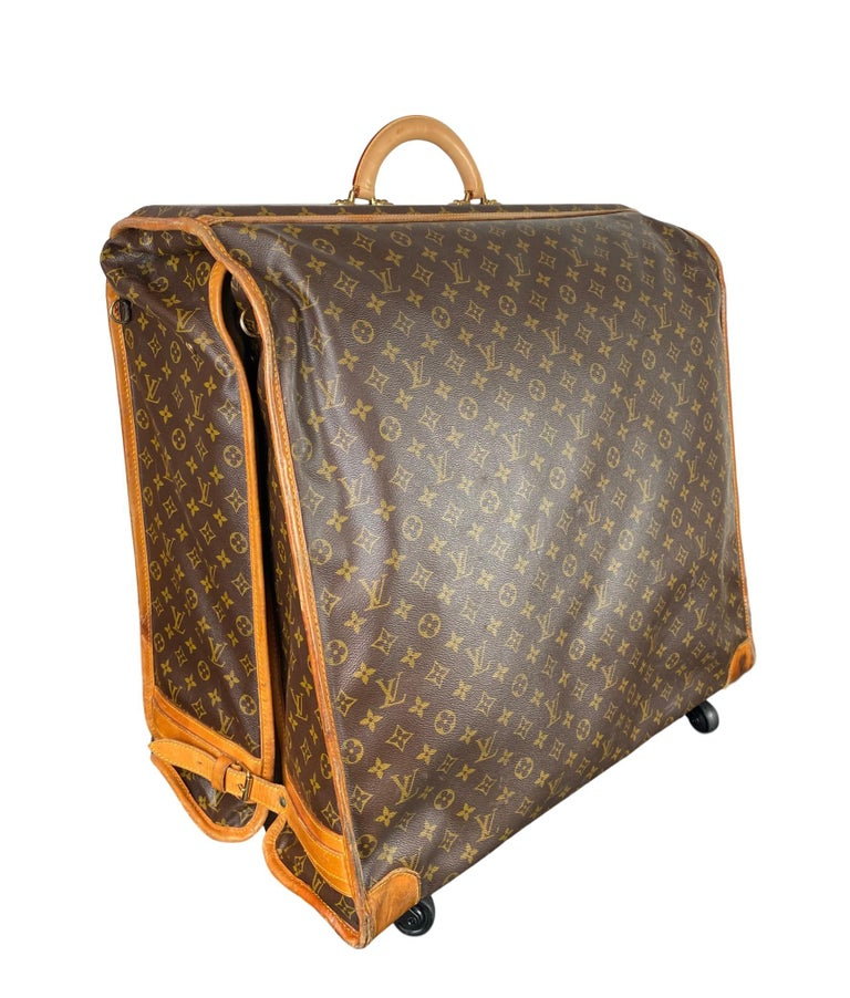 Vintage Louis Vuitton Large Folding Garment Monogram Luggage, circa 1970. This rare vintage garment bag comes in the classic Louis Vuitton Monogram canvas with a brand new rolled top vachetta handle, original vachetta pipping, buckle lock closures