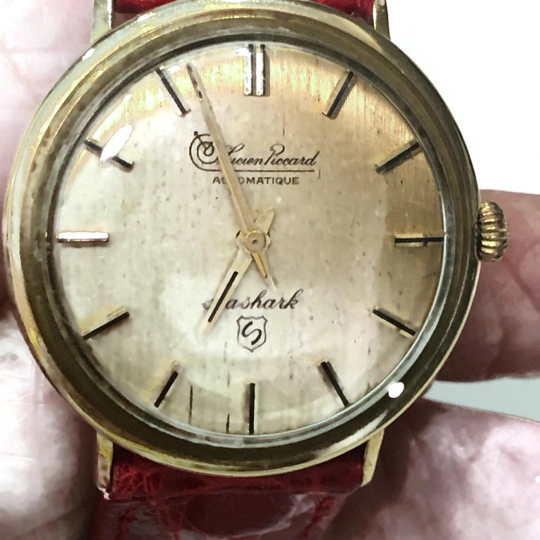 Vintage Lucien Piccard automatic movement 14k yellow gold  watch with a round face and a red crocodile band.  The watch is in a classic style.  The watch is in mint condition  Although it is a Vintage watch, it is totally in style today.  A