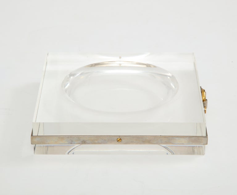 A chic Lucite vide poche with nickel band and brass buckle detail, France, 1970s. Unsigned, in the manner of Hermes and Gucci.