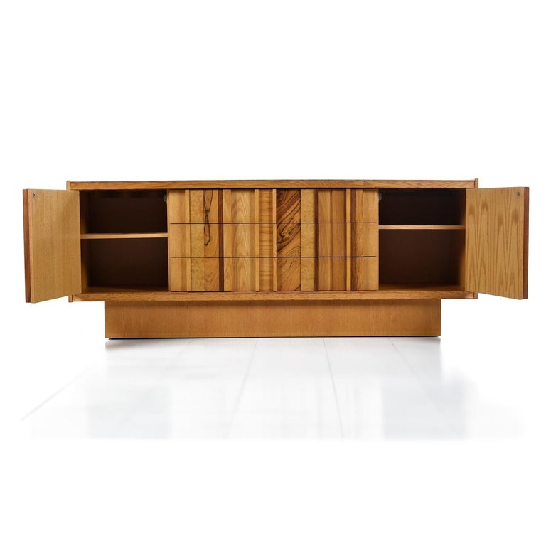 This stunning Brutalist credenza use several species of wood to create a truly unique look. The magpie assortment of veneers include maple, oak, burl wood, rosewood and walnut. The main body of the piece is a honey colored maple, fitting for this