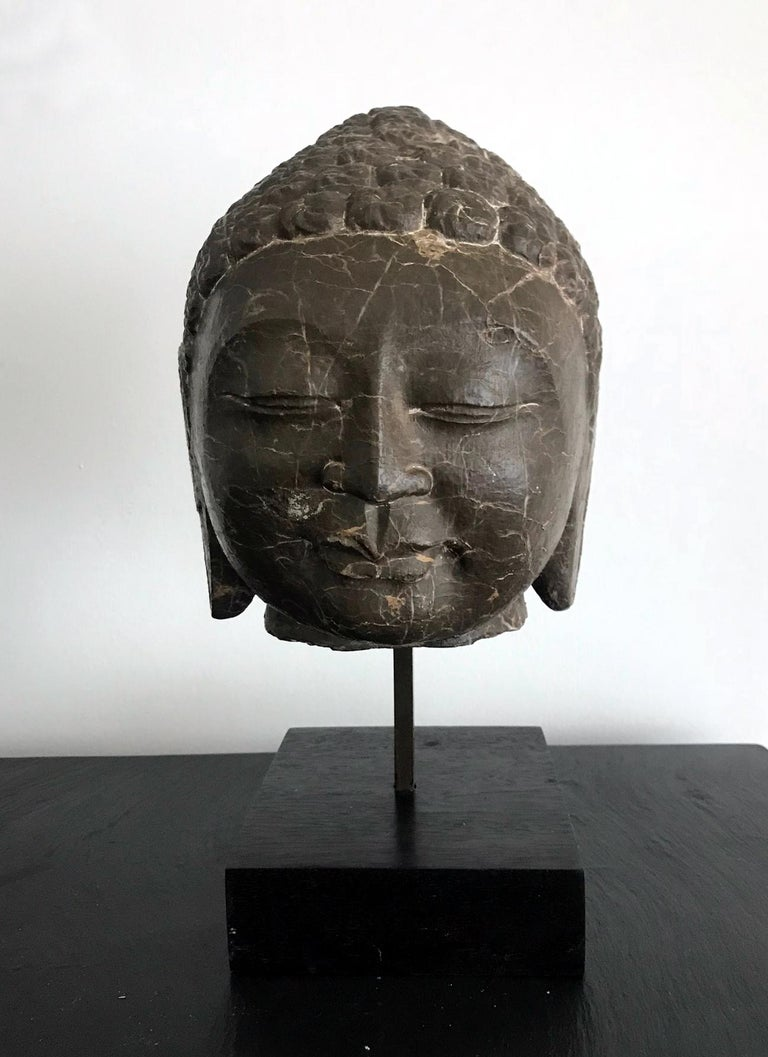 Carved out of a heavy block of dark brown marble with striking white veins, this Buddha head represents the Northern Qi style in China (550-577), but we believe that it was likely carved in the 20th century as a study for classic Buddhism sculpture.