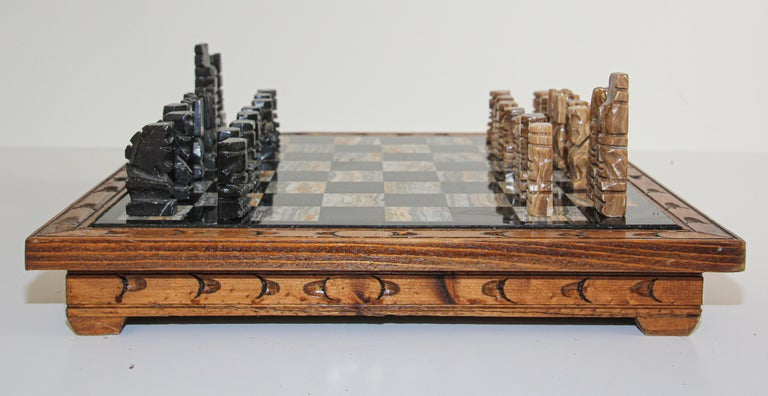 Vintage large heavy marble chess set complete board in brown and black with chess set with marble Mexican hand carved chess pieces. Carved Aztec onyx black and beige chess pieces. The chess board is mounted on a wooden handcrafted stand with