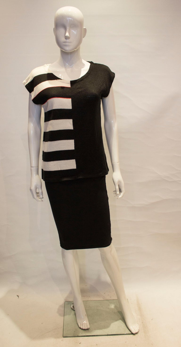 A chic vintage top by Mary Quant. The top has a round neckline and cap sleeves, and is stripes on one  half and block colour on the other, front and back.